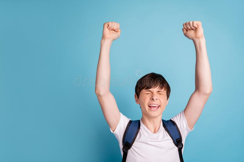 Photo of enjoying cheerful nice boy celebrating his victory at volleyball contests while isolated with blue background stock photography