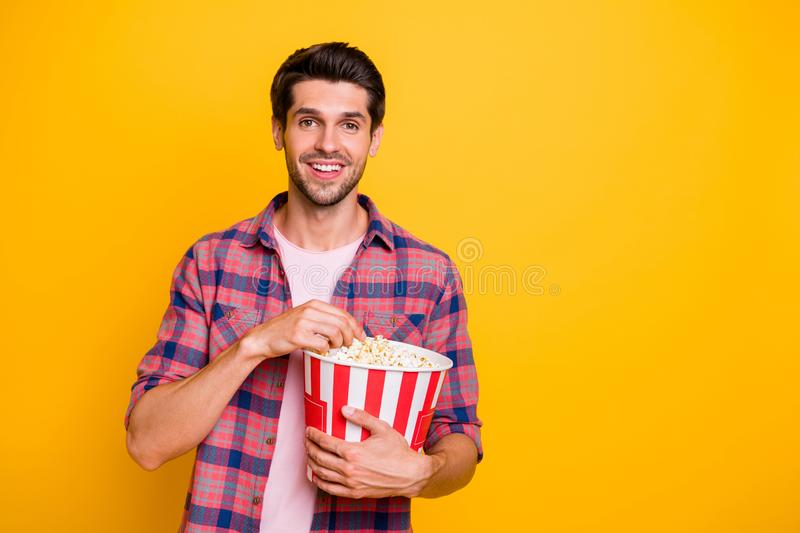 Photo of enjoying man watching his favorite movie and eating pop corn while isolated with yellow background. Photo of enjoying man watching, his favorite movie stock photos