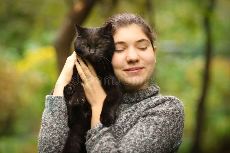Photo ensoleillée d'été de blackcat d'étreinte de fille d'adolescent photographie stock
