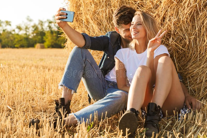 Photo of european couple man and woman taking selfie while sitting under big haystack in golden field, during sunny day. Photo of european couple men and women stock photography