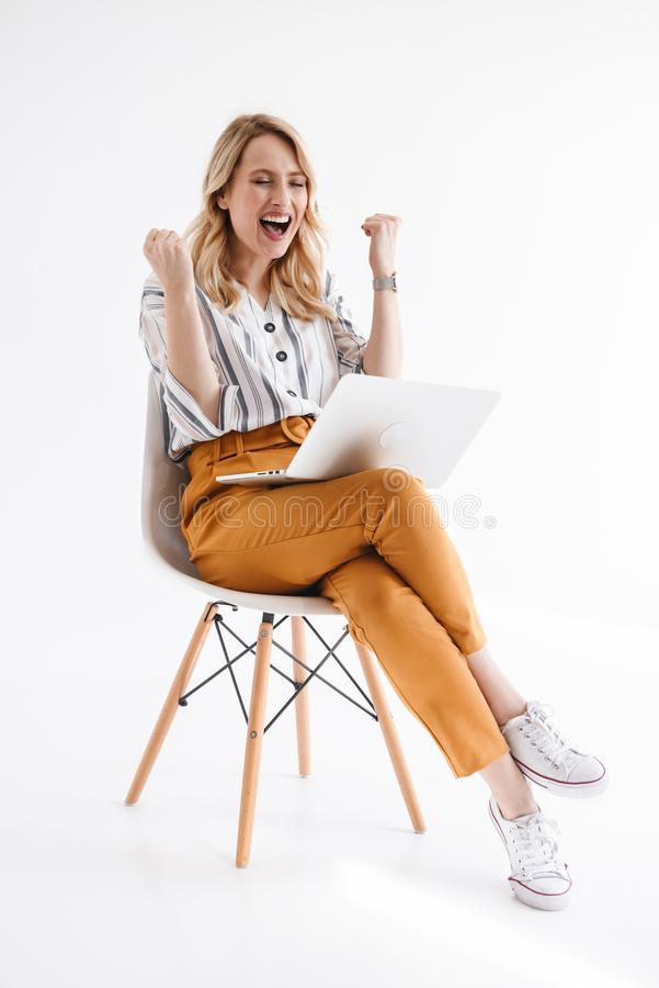 Photo of european happy woman wearing casual clothes using laptop while sitting in chair stock image