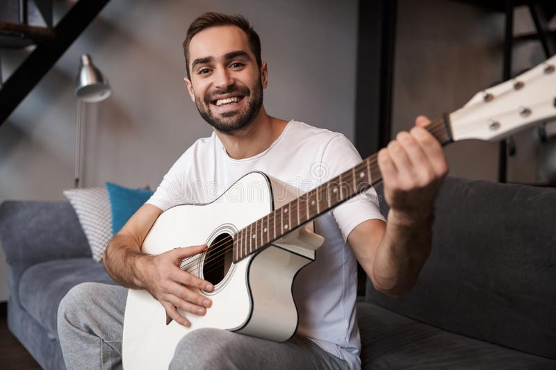 Photo of european man playing acoustic guitar while sitting on sofa in apartment stock images