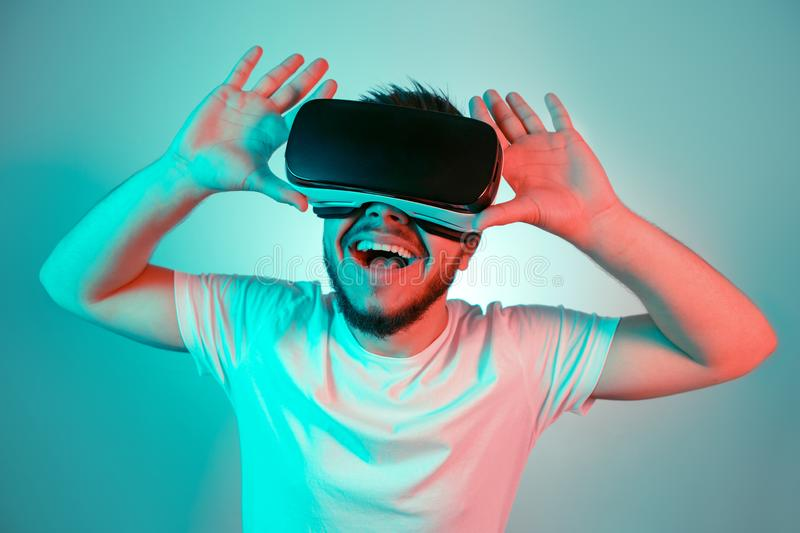 Photo of excited bearded man trying VR headset and exploring another world on the colorful background. Smartphone using royalty free stock images