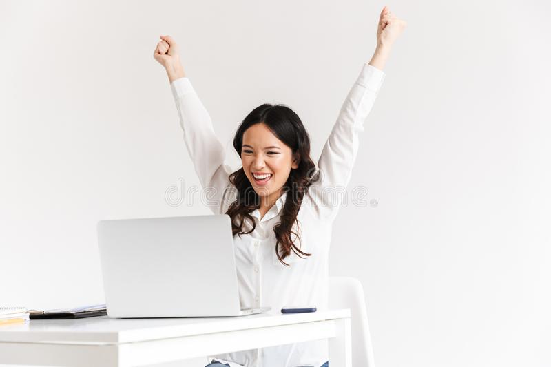 Photo of excited chinese businesswoman with long dark hair screaming with raised arms and celebrating success while working in stock photography