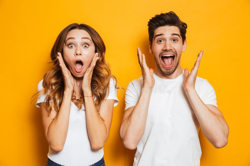 Photo of excited couple man and woman in basic clothing shouting. Photo of excited couple men and women in basic clothing shouting in surprise or delight and stock image