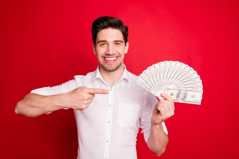 Photo of excited man showing pointing symbol at his money he just received while isolated with red background. Photo of excited man showing pointing, symbol at stock photo
