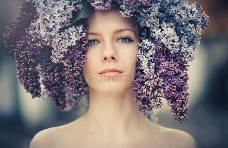 Photo extérieure de mode d'une belle jeune femme aux yeux bleus Couleur de ressort belle fille blonde en fleurs lilas Parfum avec photo stock