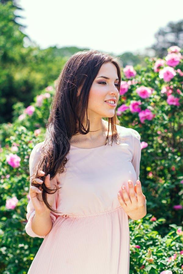 Photo extérieure de mode de la belle jeune femme de sourire heureuse entourée par des fleurs Fleur de source photographie stock
