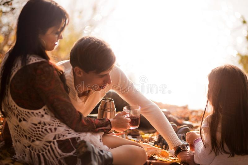 Family picnic in the autumn park. Family drinking tea stock image