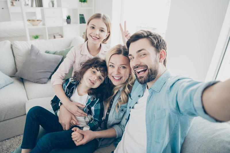 Photo of family two children taking selfies toothy smiling making v-sign symbol hand generation bonding royalty free stock photography