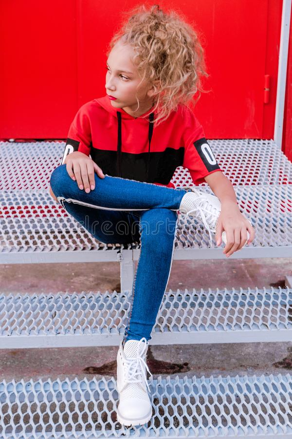 Fashionable teenager girl posing on a red wall background, sitting on the stairs royalty free stock photo
