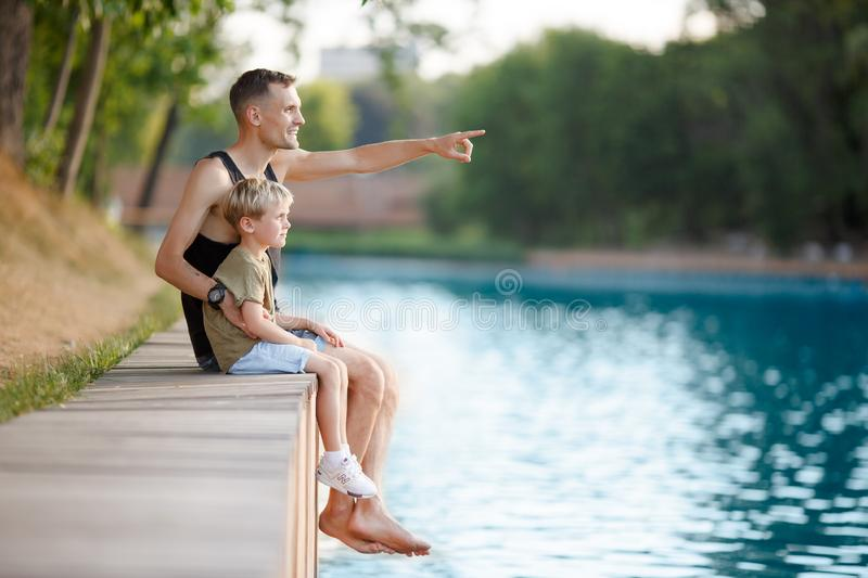 Photo of father and boy sitting on wooden bank by river royalty free stock images