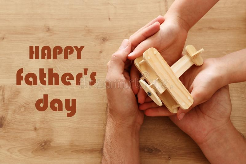 Photo of father and little child holding together wooden toy plane. Happy father`s day and holiday concept. top view, above.  stock image
