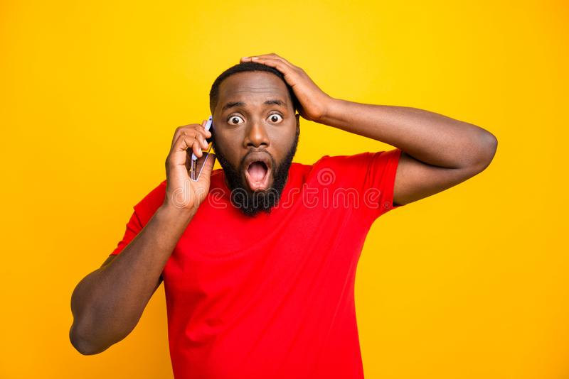 Photo of feared trembling black man with his hand holding head hearing some bad news while talking by phone while. Photo of feared trembling, black man with his stock image