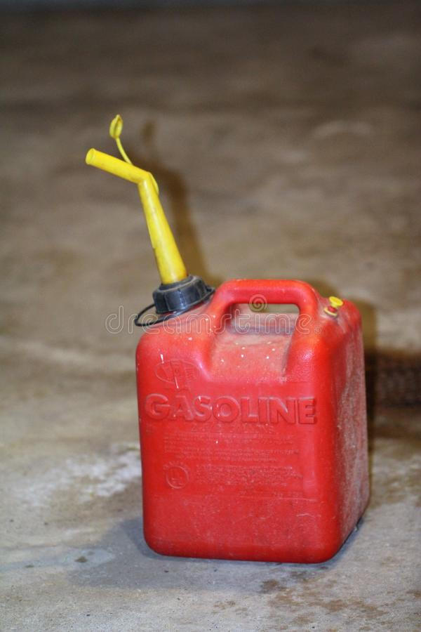 Dusty red plastic gas can with a yellow spout on a garage floor stock image