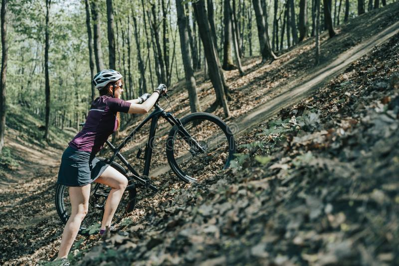 Photo of female athlete in helmet raising bicycle to hill in forest royalty free stock photography