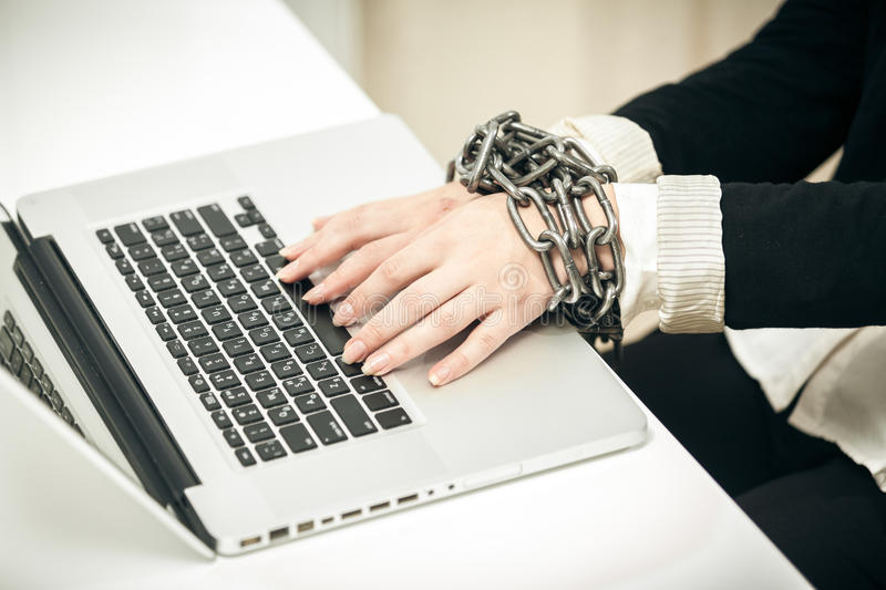 Photo of female hand chained up to laptop royalty free stock images