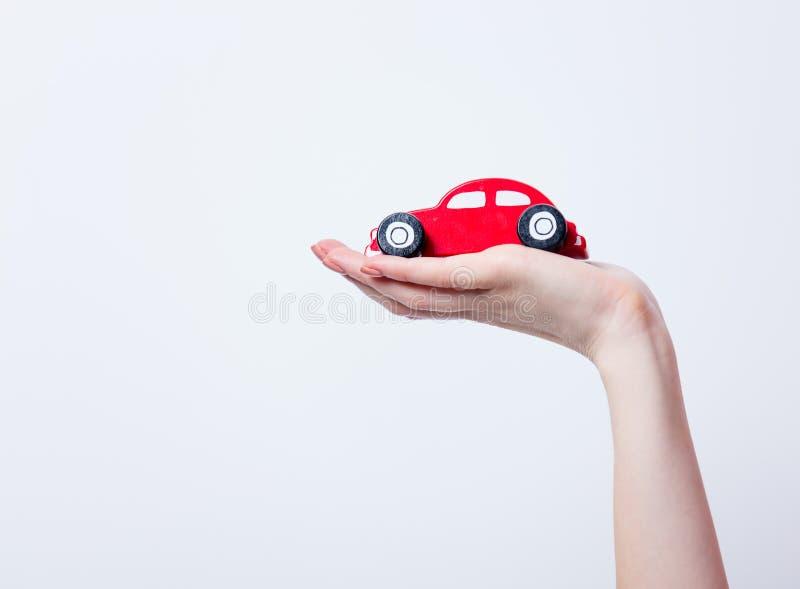 Photo of female hand holding car shaped toy on the wonderful whi stock photos