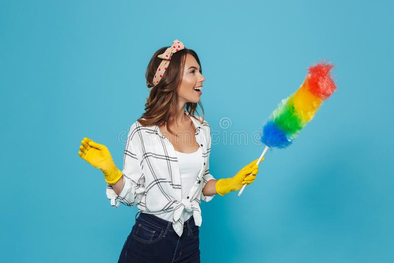 Photo of female houseworker 20s in yellow rubber gloves for hand royalty free stock photography