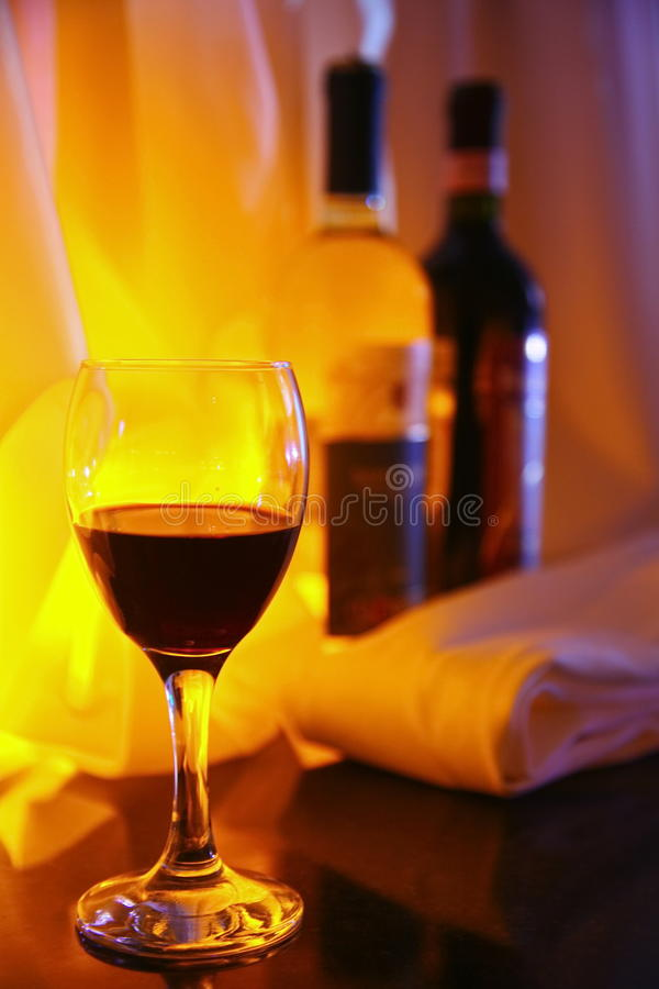 Photo-filled red wine glass transparent glass on the background of two full bottles of red and white wine. Against the yellow decorative lighting, fabric royalty free stock images