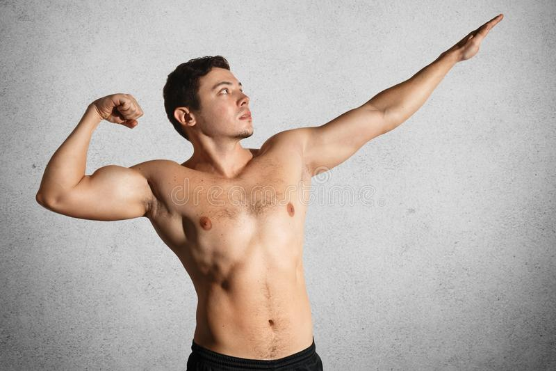 Photo of fit strong young male bodybuilder poses, shows flexed muscles, stretches hands, isolated over grey background. Fitness mo royalty free stock images