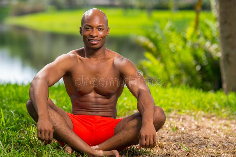 Photo of a fitness model in a yoga pose. Image lit with flash in a park setting royalty free stock image