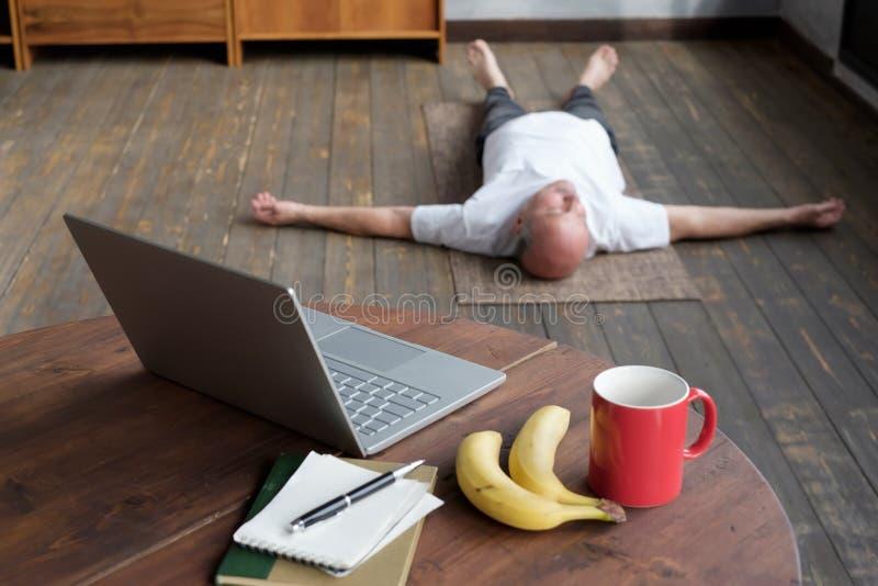Photo floue d'un homme caucasien de haut rang couché dans la pose de Shavasana image stock