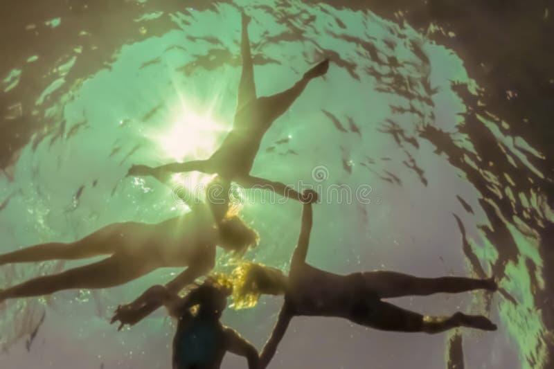 Photo floue - image abstraite pour l'arrière-plan Des gens tenant la main flottant à la surface de l'eau, tirant depuis le sous-s photographie stock libre de droits