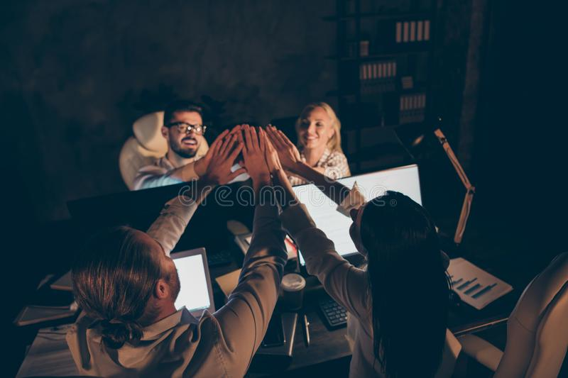 Photo of four business partners sitting table working together late night holding arms pile stack union deal one team royalty free stock photo