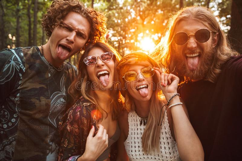 Photo of four hippie people men and women, smiling and taking se stock photo
