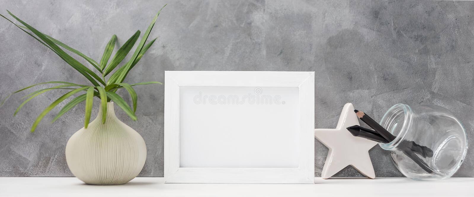 Photo frame close up mock up with palm leaves in vase, ceramic star, pen and pencil in mason jar on shelf. Scandinavian style royalty free stock photography