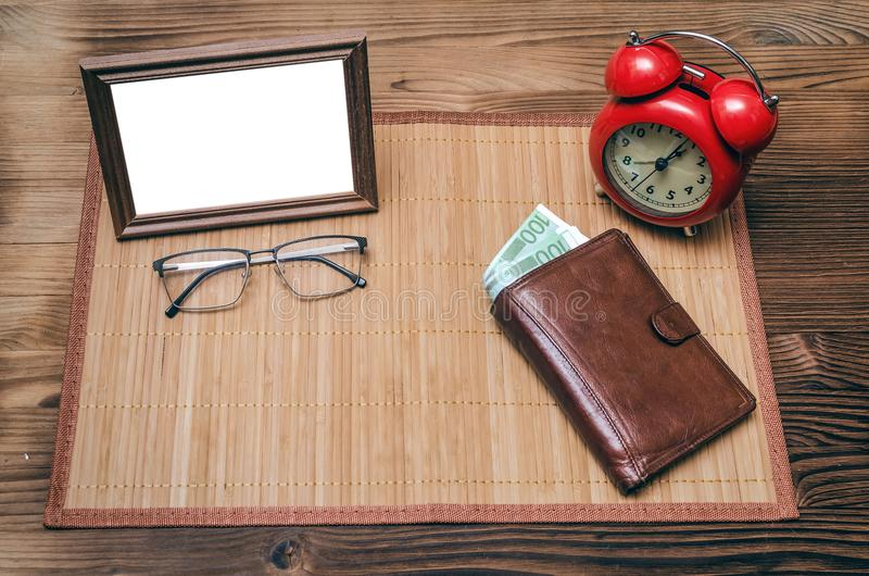 Photo frame with copy space and retro style alarm clock, wallet with money. royalty free stock images