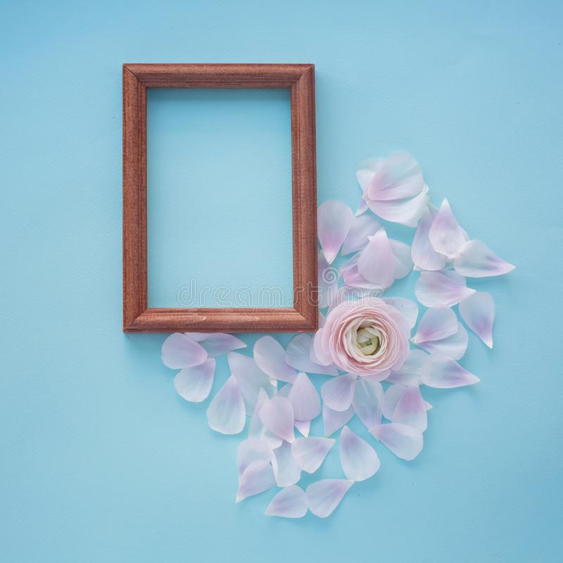 Photo frame heart of light pink petals on a light blue square textural background with a flower in the center. Photo frame heart of light fresh delicate pink royalty free stock photo