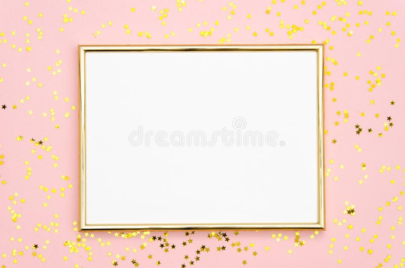 Photo frame mock up with space for text, golden sequins confetti on pink background. Lay Flat, top view. Valentine`s royalty free stock photo