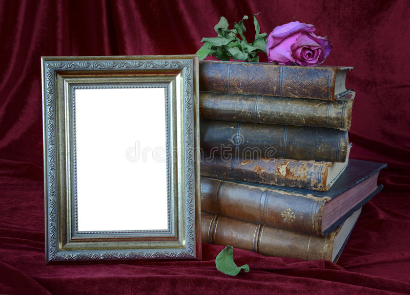 Photo frame and stack of antique books stock photos