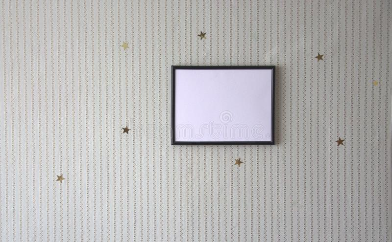 Photo frame on the wall, decor of gilded asterisks and stripes. Novosibirsk stock image