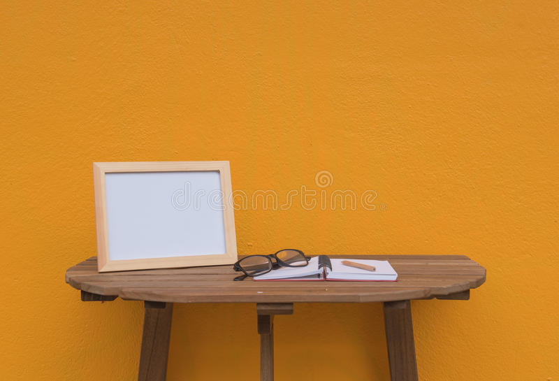 Photo Frame on a wooden table and book and Yellow background . stock photography