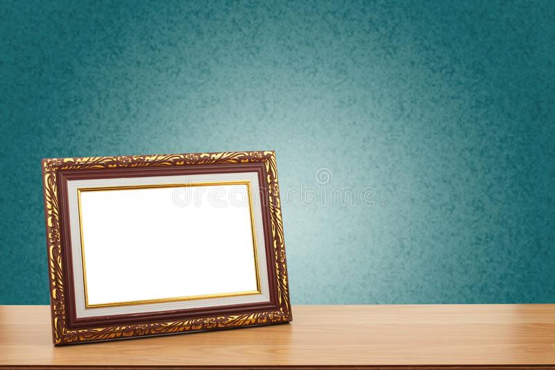 Photo frame on wooden table over green wall background royalty free stock photo