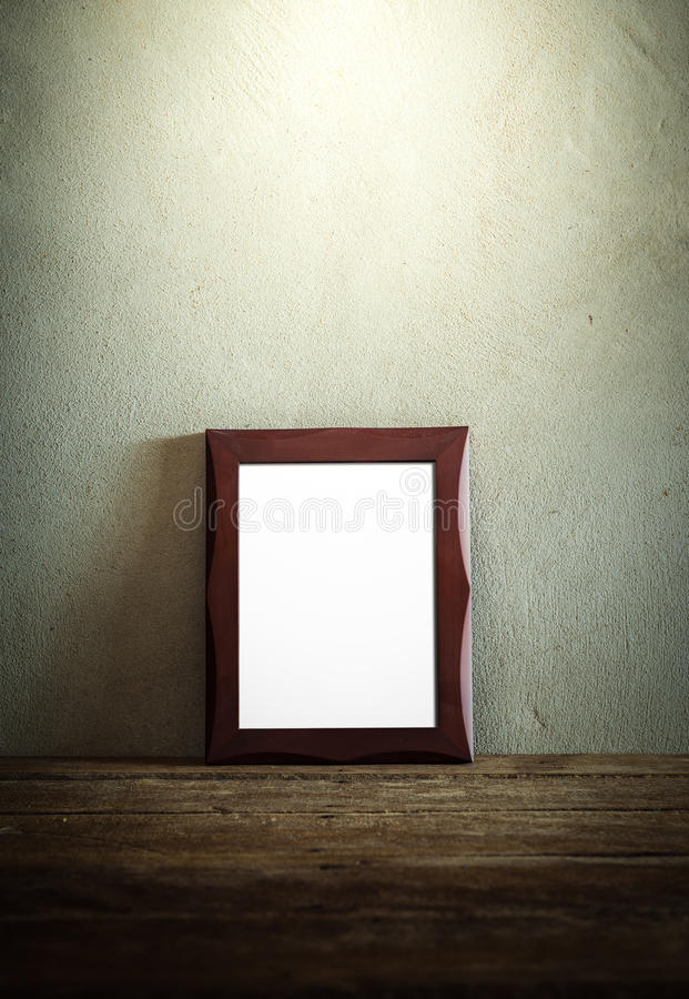 Photo frame on wooden table over grunge background stock photography