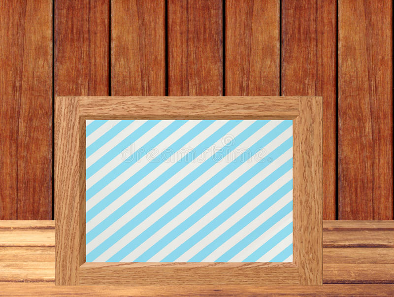 Photo frame on wooden table over wooden background stock image