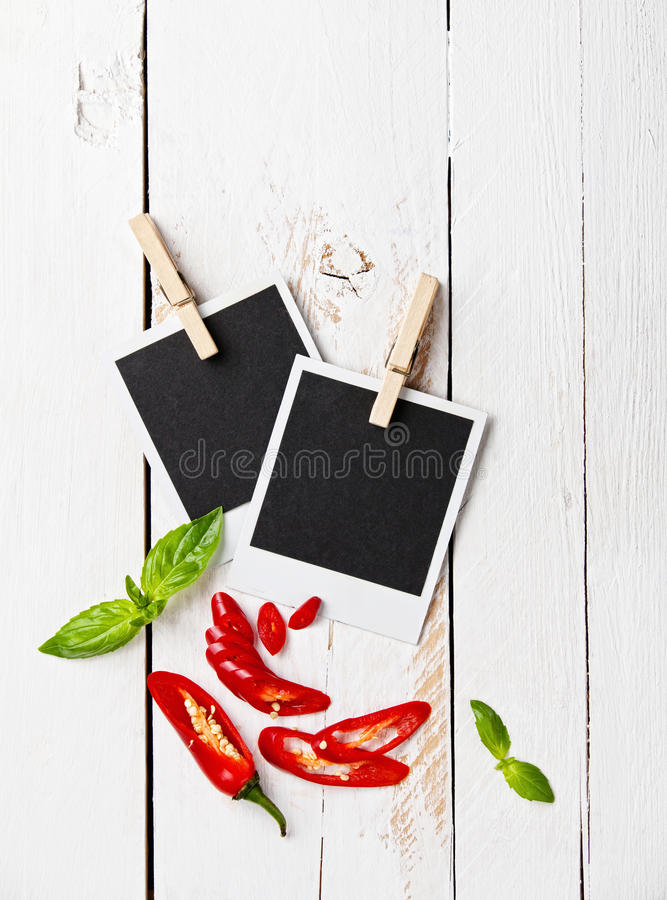 Photo frames. Hanging aged photo frames with chili pepper on wooden background royalty free stock image