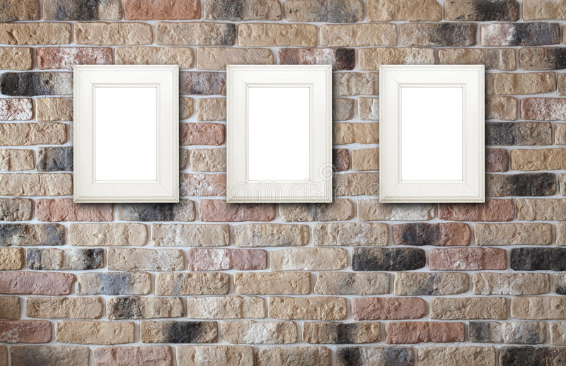 Photo frames on brick wall