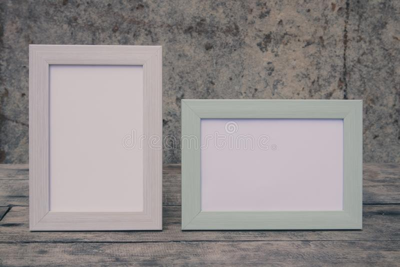 Photo frames on the retro wooden table with stone wall background stock photo