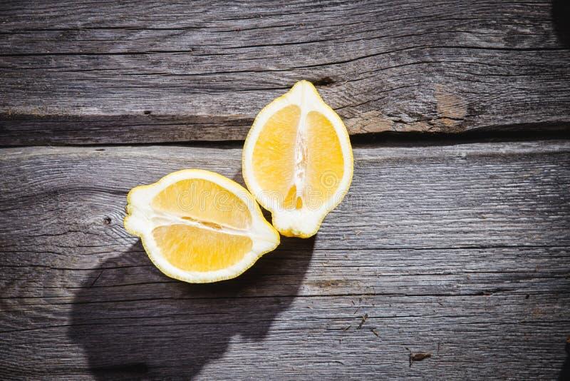 Photo of fresh ripe lemons on retro background. A slice of lemon with green leaves. Lemon fruit on wooden plate bowl. Lemon around stock images