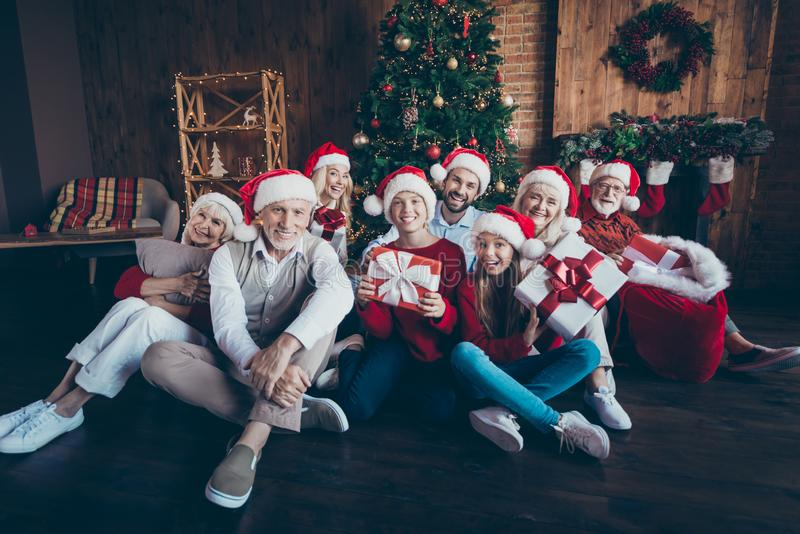 Photo of friendly big large family smiling toothily having new year party together sitting on floor in santa cap royalty free stock photo