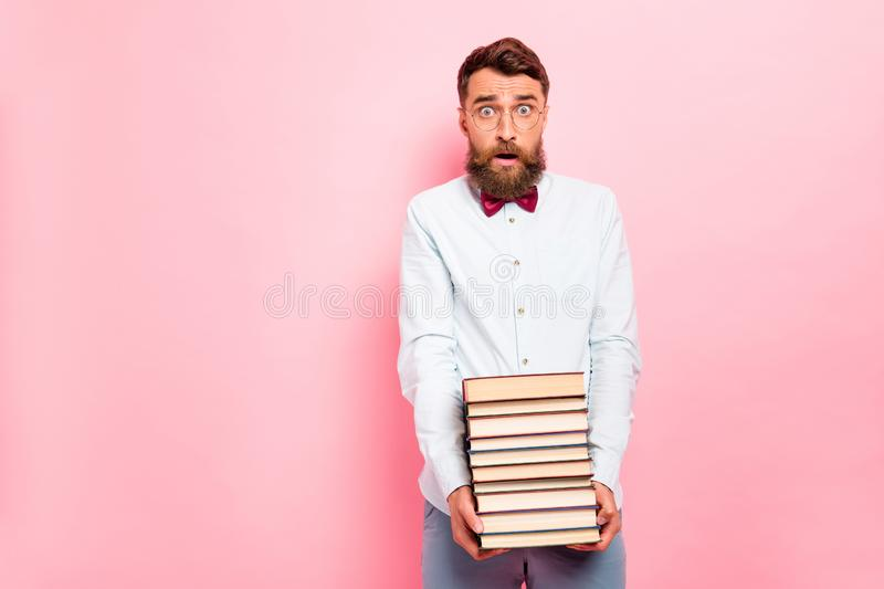 Photo of frustrated astonished saying omg person holding great pile of books in hands wearing white shirt isolated. Photo of frustrated astonished saying omg stock photo