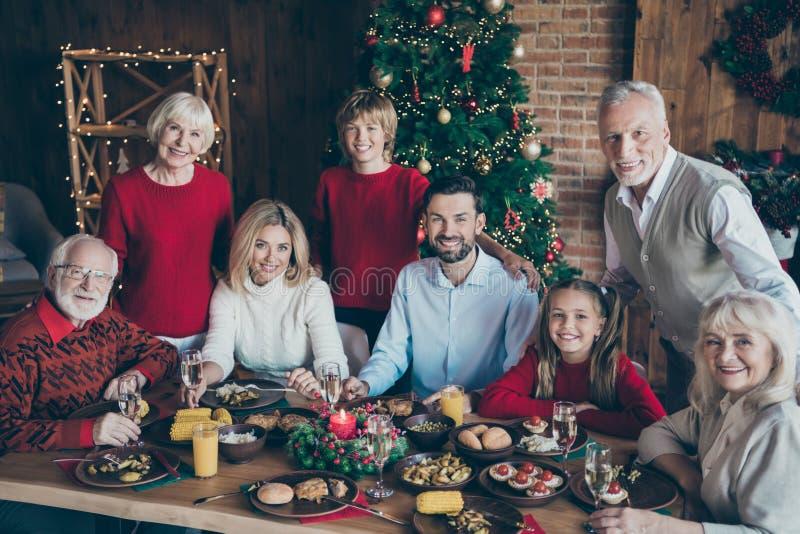 Photo of full family gathering around dinner table generation reunion posing hugging for holiday portrait in x-mas. Photo of full family gathering around dinner stock image
