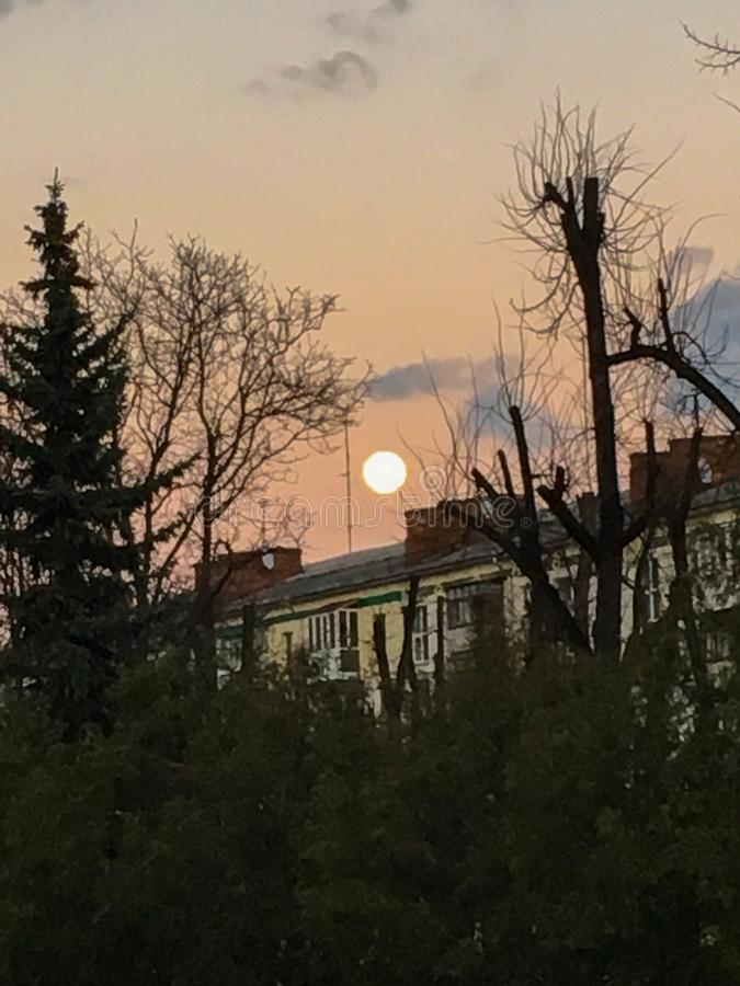 The photo of the full moon on the cloudy sky above the building in the park. Halloween background royalty free stock photo
