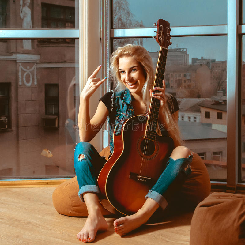 Photo of fun blonde woman with guitar and beautiful smile royalty free stock image
