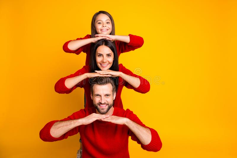 Photo of funky cheerful nice cute charming family shaping pyramid by laying hands on each others heads creating stock images